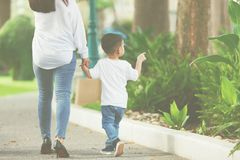 Mom and son take hand in hand. Mom and son take hand in hand together between walk at the park at weekend stock photos