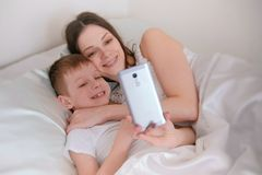Mom and son take selfie on her mobile phone. Morning in bed. royalty free stock photo