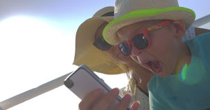 Mom and son taking funny selfie on the yacht. Happy mother and son traveling by sea and taking selfie on mobile, boy making funny faces. Journey on sunny summer stock footage
