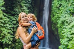 Mom and son travelers on the background of Leke Leke waterfall in Bali island Indonesia. Traveling with children concept.  stock photo