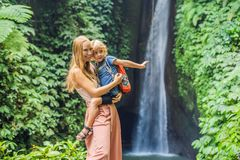 Mom and son travelers on the background of Leke Leke waterfall in Bali island Indonesia. Traveling with children concept.  stock image