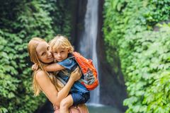 Mom and son travelers on the background of Leke Leke waterfall in Bali island Indonesia. Traveling with children concept.  stock photos