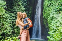 Mom and son travelers on the background of Leke Leke waterfall in Bali island Indonesia. Traveling with children concept.  stock images