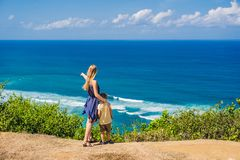 Mom and son travelers on a cliff above the beach. Empty paradise stock photos