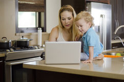 Mom and son using a laptop. Young mother and her son looking at something in a laptop on the kitchen counter stock photography