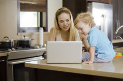 Mom and son using a laptop. Young mother and her son looking at something in a laptop on the kitchen counter royalty free stock images