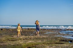 Mom and son are walking along the cosmic Bali beach.. Portrait travel tourists - mom with kids. Positive human emotions. Active lifestyles. Happy young family stock photos