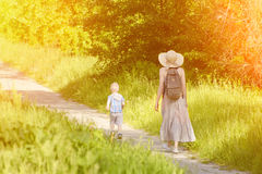Mom and son walking along the road in the park. Back view. Sunny day.  Stock Photos