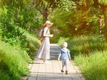 Mom and son walking along the road in the park. Back view. Vertical frame royalty free stock photo
