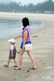 Mom and Son Walking on Beach Stock Image