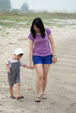 Mom and Son Walking on Beach Royalty Free Stock Photos