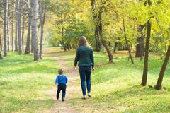 Mom and son walking in the park at sunset stock image