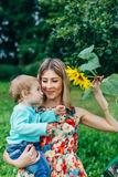 Mom and son watching flowers. Mom and son walk in the park outside the city in the evening Stock Photos