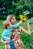 Mom and son watching flowers. Mom and son walk in the park outside the city in the evening Royalty Free Stock Images