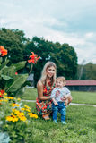 Mom and son watching flowers. Mom and son walk in the park outside the city in the evening Stock Image
