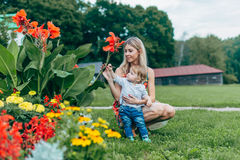 Mom and son watching flowers. Mom and son walk in the park outside the city in the evening Royalty Free Stock Photos