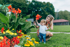 Mom and son watching flowers. Mom and son walk in the park outside the city in the evening Stock Photo