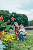 Mom and son watching flowers. Mom and son walk in the park outside the city in the evening Royalty Free Stock Photo