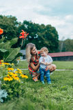 Mom and son watching flowers. Mom and son walk in the park outside the city in the evening Royalty Free Stock Photography