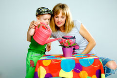 Mom and son watering flowers with a watering can Stock Images