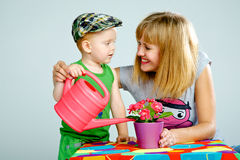 Mom and son watering flowers with a watering can. Studio white background Stock Photo