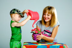 Mom and son watering flowers with a watering can. Studio white background Royalty Free Stock Images