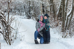 Mom and son in the winter. Beautiful young mother walking with her son in the winter forest Stock Photos
