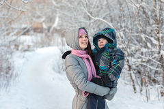Mom and son in the winter. Beautiful young mother walking with her son in the winter forest Stock Photography