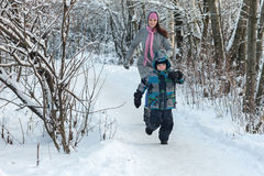 Mom and son in the winter. Beautiful young mother walking with her son in the winter forest Royalty Free Stock Image