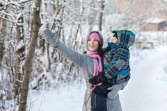 Mom and son in the winter. Beautiful young mother walking with her son in the winter forest Stock Image