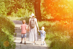 Mom and sons walking along the road in the park. Back view. Sunny day.  Stock Images