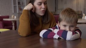 Mom soothes the little son who was offended by her sitting at a table in a cafe stock video footage
