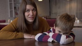 Mom soothes the little son who was offended by her sitting at a table in a cafe stock footage
