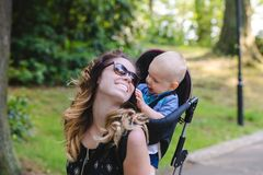 Free Mom Spends Time With Her Little Son. He Wears It In A Baby Carrier. I Walk In The Park And Smile. Stock Photo - 154426000