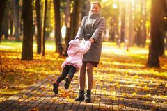 Mom is spinning daughter in autumn colorful park on sunny day. Mother and daughter playing circling around at the park. Mom is spinning daughter in aun colorful royalty free stock image