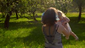 Mom is spinning with a little girl in her arms. Mommy is spinning with a charming little girl in her arms in the garden stock footage