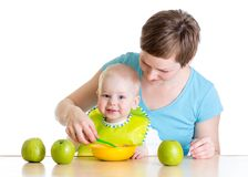 Mom spoon feeding her baby Royalty Free Stock Image