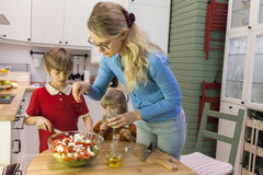 Mom sprinkle the salad with herbs. Children helping mother on the kitchen Royalty Free Stock Images