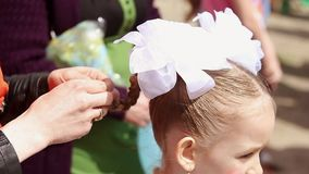 Mom straightens the pigtails of her daughter. Beautiful little daughter, prepare for the holiday. stock footage