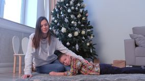 Mom stroking son on back near Christmas tree at home in living room, New Year. stock footage