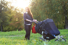 Mom with stroller walks in autumn park alley Royalty Free Stock Photos