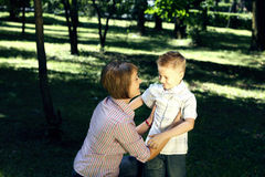 Mom and sun hugging outdoors Royalty Free Stock Image