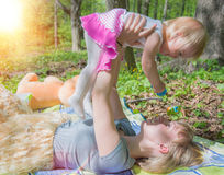Mom on a sunny day playing with his daughter in the green park. Mom on a sunny day playing with his daughter in a green park, joyful emotions baby Royalty Free Stock Photo