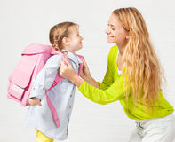 Mom support child to wear a backpack Royalty Free Stock Photo
