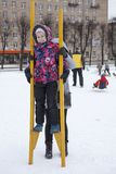 Mom supports from the back of the child standing on wooden stilts at winter. Social activity are at Maslenitsa holiday, Russia. Mom supports from the back of the Royalty Free Stock Photos