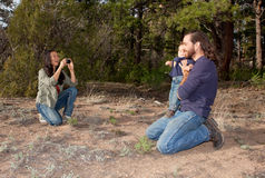Mom taking a picture of son and dad. Mother taking a picture of father and son outdoors in nature Royalty Free Stock Photo