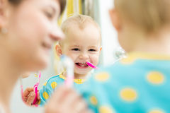Mom teaches baby brushing teeth royalty free stock photo