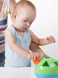Mom teaches the baby to put toys. Studio shoot Stock Photo