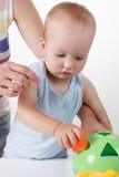 Mom teaches the baby to put toys. Studio shoot Stock Image