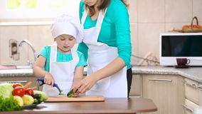 Mom teaches child to clean cucumber stock footage